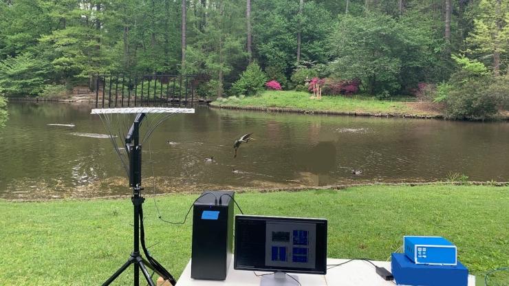 Electronics set up on a folding table by a pond