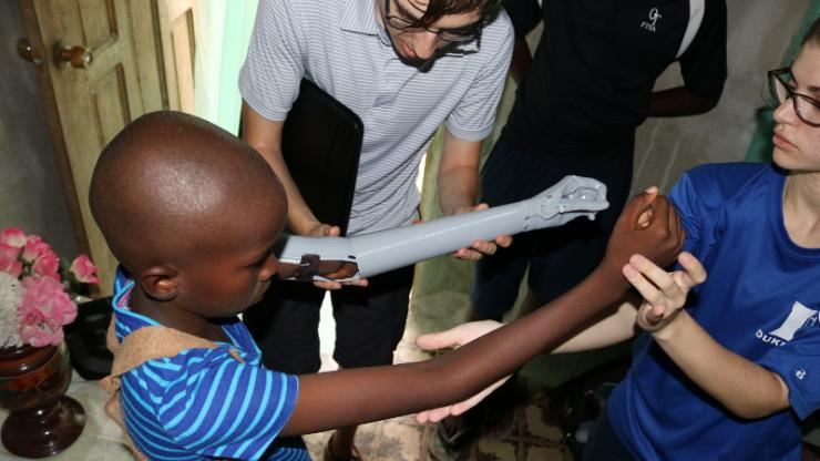 Emily Shannon and Gabriel Antoniak test the length of the first prototype prosthetic arm while the recipient tries it on during their first trip to Haiti