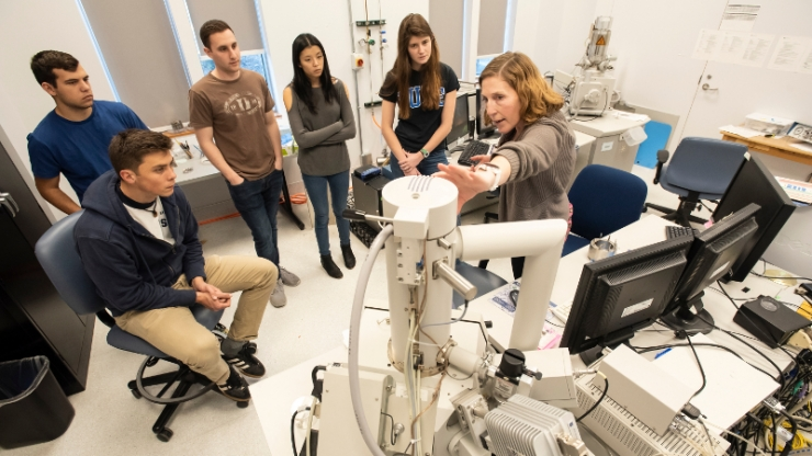 A group of students watch a researcher explain a large technical piece of equipment