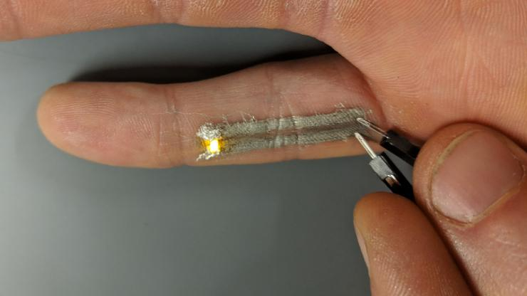 A pinky with two gray lines on the underside with an electrode at one end and a lit-up LED at the other
