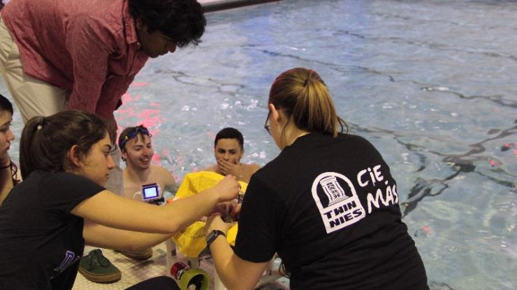 A team in EGR 190 gathers poolside with its submersible robot