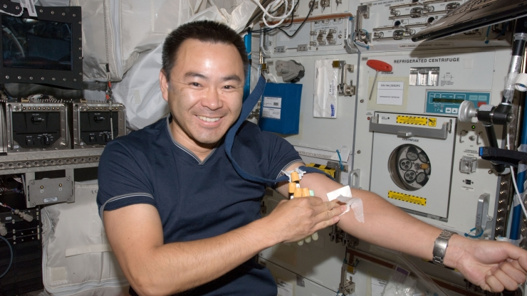 astronaut after having blood drawn from arm