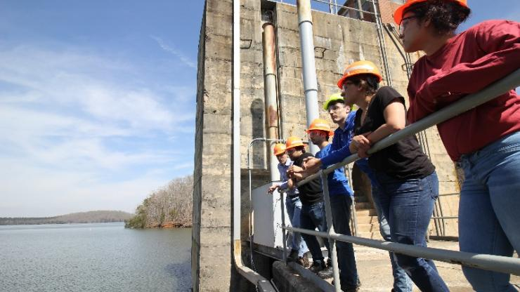 A group of mechanical engineering students gather at hydroelectric facility