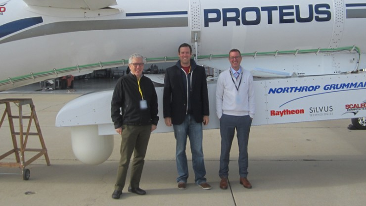 Three men stand in front of a plan that says Proteus on the side