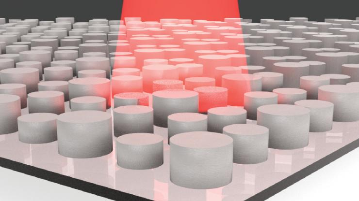 Array of small gray cylinders of different sizes on a grey sheet with a red beam of light hitting a small section