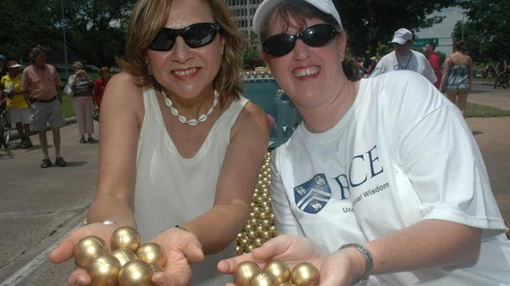 Naomi Halas and Jennifer West holding large golden spheres at a parade