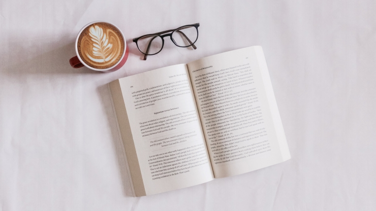Open book with reading glasses and cup of coffee