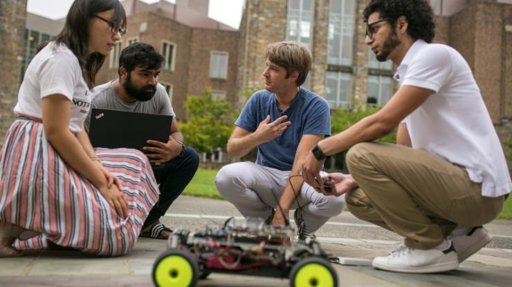 Miroslav Pajic kneeling with research group and small toy car