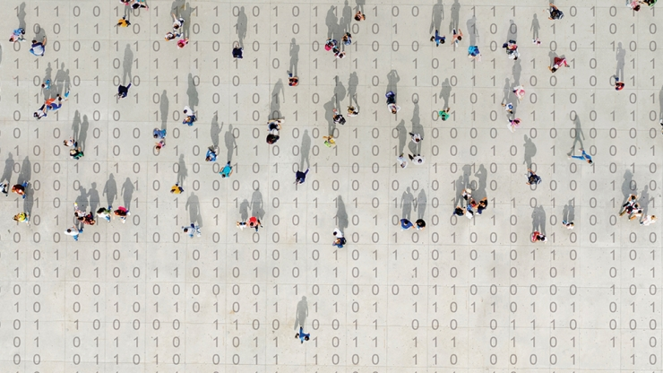 People walk atop binary code