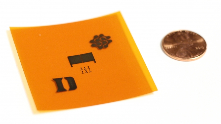A demonstration of the printed carbon nanotubes on a flexible surface. The prototype tire tread sensor (middle) is flanked by the logos of Duke University and Fetch Automotive Design Group.
