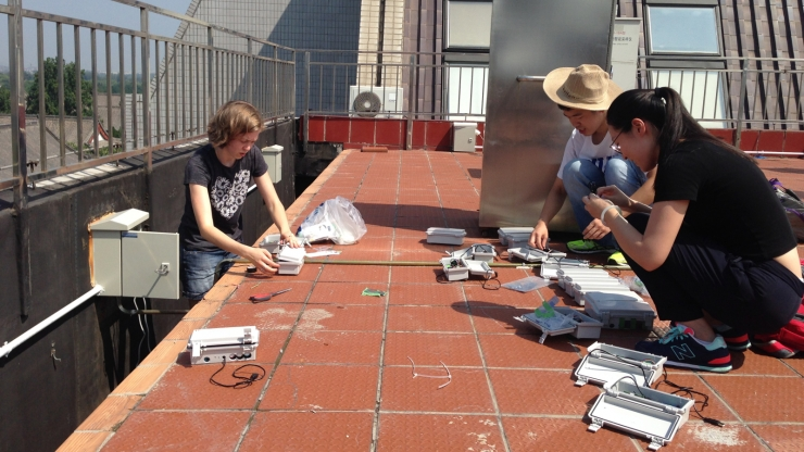 Three students sit on a tiled rooftop working on electronics