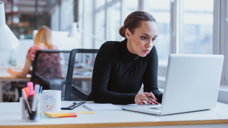 female working at laptop in office