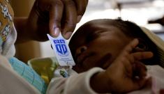 A woman in Tanzania gives her newborn baby antiretroviral drugs from a Pratt Pouch.