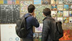 Students peruse entries in AI art competition