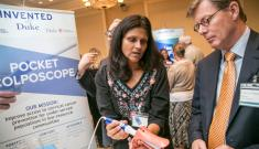 BME's Nimmi Ramanujam demonstrates the Pocket Colposcope to Duke University President Vincent Price. The invention is a low-cost device that helps screen for and diagnose cervical cancer.