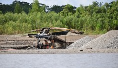 A riverbank cleared of vegetation with simple machines and piles of soil