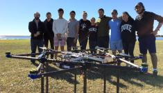 Duke Engineering students stand with their prototype heavy-lifting drone after a test flight for the Ocean Discovery XPRIZE competition.