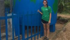 Elizabeth Griffin in front of rainwater catchment tank