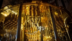 complex machinery with vials and tubes hanging down from a circular ceiling all bathed in yellow-gold light
