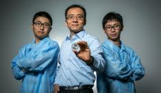 Tony Jun Huang holds out a tiny prototype device while flanked by two graduate students