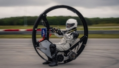 A person in a protective suit riding inside of a giant wheel