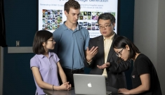 Four people stand around an open computer with a projector screen in the background