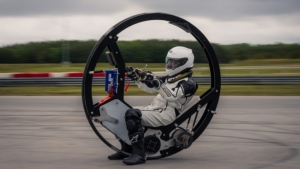 person inside protective suit riding inside electric monowheel