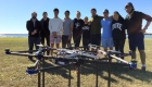 team stands with xprize drone