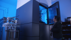 A woman stares up into a giant box with a soft blue light inside