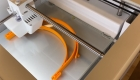 A 3D printer printing out an orange headband for a face shield