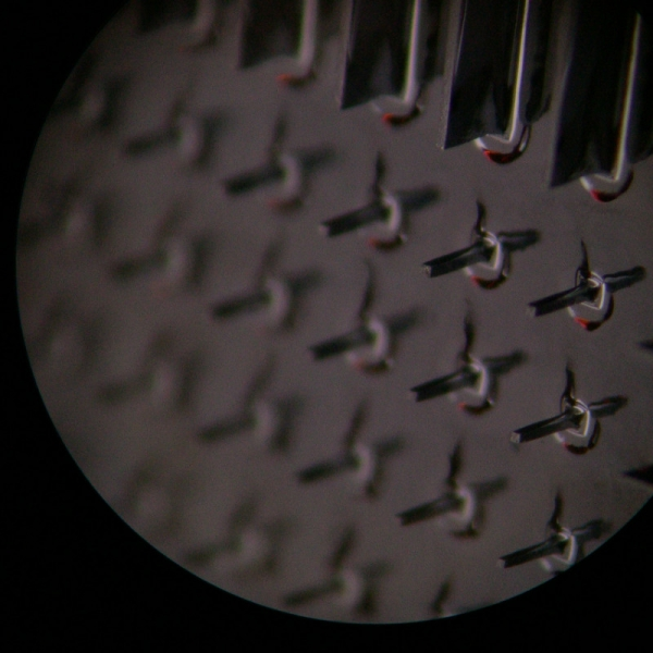A microscope image of tiny needles etched on a silicon wafer by Zach Brown.