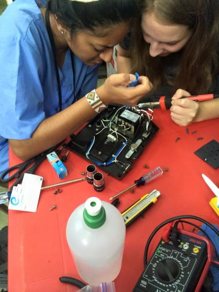 Raina Kishan and Zoe Roecker fixing a microscope while working in the San Jose Hospital in Diriamba, Nicaragua.