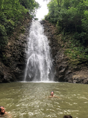 Students swim in a pool at the base of a waterfall in the jungle